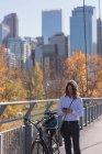 Человек с помощью мобильного телефона, стоя с велосипедом на мосту в городе — стоковое фото