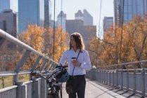 Человек с помощью мобильного телефона во время прогулки на велосипеде по мосту в городе — стоковое фото