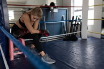 Tired female boxer relaxing in boxing ring at fitness studio — Stock Photo