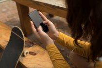 Gros plan de skateur femelle à l'aide de téléphone portable au café en plein air — Photo de stock