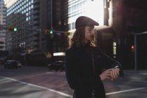 Hombre comprobando el tiempo de guardia mientras camina por la calle en la ciudad - foto de stock