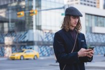 Homem usando o celular enquanto caminhava na rua na cidade — Fotografia de Stock