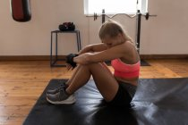 Tired female boxer relaxing in fitness studio — Stock Photo