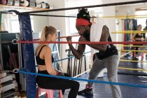 Male trainer assisting female boxer in boxing ring at fitness studio — Stock Photo