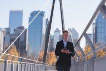 Uomo che usa il telefono cellulare mentre cammina sul ponte in città — Foto stock