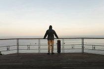 Rückansicht eines männlichen Skateboarders, der an einem Geländer am Beobachtungspunkt steht — Stockfoto
