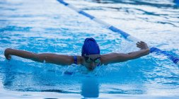 Front view of female swimmer swimming butterfly in swimming pool — Stock Photo