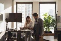 Vista laterale degli uomini d'affari in piedi che discutono sui documenti nell'ufficio moderno — Foto stock