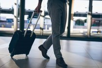 Low-section of a businessman walking with his travel suitcase in the office — Stock Photo