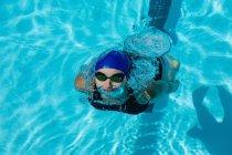 Vista de ángulo alto de la nadadora joven nadando estilo libre en la piscina - foto de stock