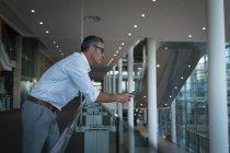 Вид збоку вдумливі бізнесмена зі своїм телефоном, спершись на перила в офісі — стокове фото