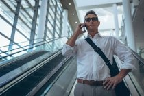 Front view of a businessman talking on the mobile phone while descending on the escalator in a modern office — Stock Photo