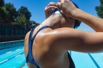 Крупный план молодой белой пловчихи в плавательных очках в бассейне под солнцем — стоковое фото