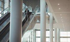 Дальний взгляд бизнесмена с портфелем разговаривающего по телефону на эскалаторе в офисе — стоковое фото