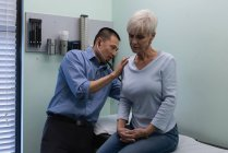 Young Asian male doctor examining a senior patient in the clinic — Stock Photo