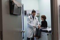 Visão frontal de jovem asiático médico masculino examinando caucasiano menino paciente com glicosímetro na clínica — Fotografia de Stock