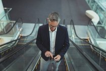 High of businessman using his mobile phone on the escalator in office — Stock Photo