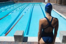 Rear view of young female swimmer standing at swimming pool in the sunshine — Stock Photo