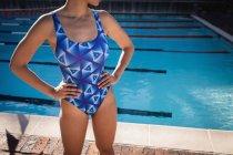 Средняя секция пловчихи, стоящая с руками на бедре возле бассейна — стоковое фото