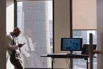 Vue latérale de l'homme d'affaires debout utilisant le téléphone portable dans le bureau moderne — Photo de stock