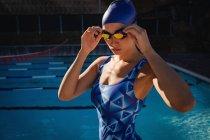 Вид спереди женщины-пловчихи в купальнике и стоящей возле бассейна — стоковое фото