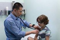 Vista lateral de joven asiático médico masculino examinando caucásico niño paciente con herramienta en una clínica - foto de stock