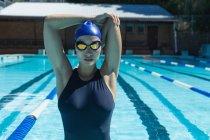 Вид спереди молодой женщины, плавающей в бассейне, растянувшейся в солнечный день — стоковое фото