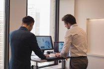 Visão traseira de empresários de pé trabalhando juntos no escritório moderno — Fotografia de Stock