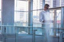 Seitenansicht eines konzentrierten Geschäftsmannes, der sein Handy im Büro benutzt — Stockfoto