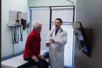 Фронтальний вид молоді азіатські чоловічого лікар взаємодіють з старший пацієнта в клініку — стокове фото