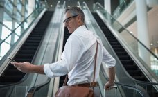 Side view of businessman checking his mobile phone on the escalator in office — Stock Photo