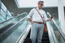 Low view of concentrated businessman checking his mobile phone on the escalator in office — Stock Photo