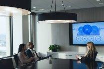 Lejos de la gente de negocios discutiendo sobre el gráfico en la sala de conferencias en la oficina - foto de stock