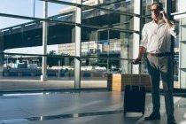 Vue de face d'un homme d'affaires tenant un sac de voyage tout en parlant sur le téléphone portable dans le bureau à côté d'une grande fenêtre montrant la ville en arrière-plan — Photo de stock
