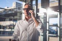 Vue rapprochée d'un homme d'affaires, parler au téléphone au bureau contre la lumière du soleil à côté de grandes fenêtres qui affichent la ville en arrière-plan — Photo de stock