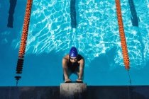 Overhead high view of a young female swimmer hanging at the handle of the starter block in swimming pool on a sunny day — Stock Photo