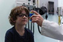 Vue de face d'un jeune médecin asiatique qui aide un garçon caucasien à utiliser un inhalateur d'asthme en clinique. Homme médecin tenant un inhalateur d'asthme. Médecin masculin interagissant avec le patient — Photo de stock