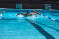 Front view of young female swimmer with swim goggle swimming at swimming pool — Stock Photo