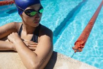 Close-up of young female swimmer standing in swimming pool — Stock Photo