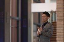 Vue latérale de l'homme d'affaires tenant un téléphone portable tout en prenant un café dans le bureau moderne — Photo de stock