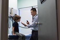 Joven asiático médico examinando un caucásico niño paciente con herramienta médica en clínica - foto de stock