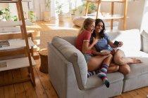 Высокий угол обзора женщин, делающих селфи дома в гостиной — стоковое фото