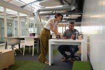 Vista frontale della gente di affari etnici multi interagire e discutere sopra una cianografia nell'ufficio — Foto stock