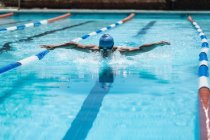 Front view of young Caucasian male swimmer in the middle of swimming butterfly stroke in outdoor swimming pool in the sunshine — Stock Photo