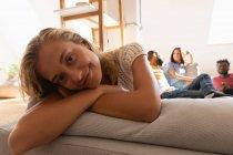 Вид спереди женщины, расслабляющейся на диване дома, глядя в камеру — стоковое фото