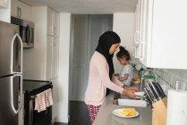 Vista lateral de la madre de raza mixta que usa hijab trabajando en la habitación de la cocina mientras su hija está sentada detrás de ella en casa - foto de stock