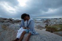 Вид спереди афроамериканской пары, сидящей и смотрящей друг на друга и расслабляющейся у моря в сумерках — стоковое фото