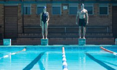 Front view of male and female Caucasian swimmers standing on the starting blocks at the swimming pool — Stock Photo