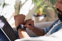 Vue latérale de l'homme afro-américain en utilisant la montre intelligente à la maison — Photo de stock
