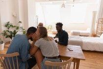 Пара сидять і взаємодіють один з одним на дому в обідній стіл. Вони весело — стокове фото